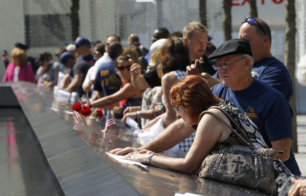 Visitors make rubbings from panels containing the names of the victims of the attacks, on the first day that the 9/11 Memorial was opened to the public at the World Trade Center site in New York