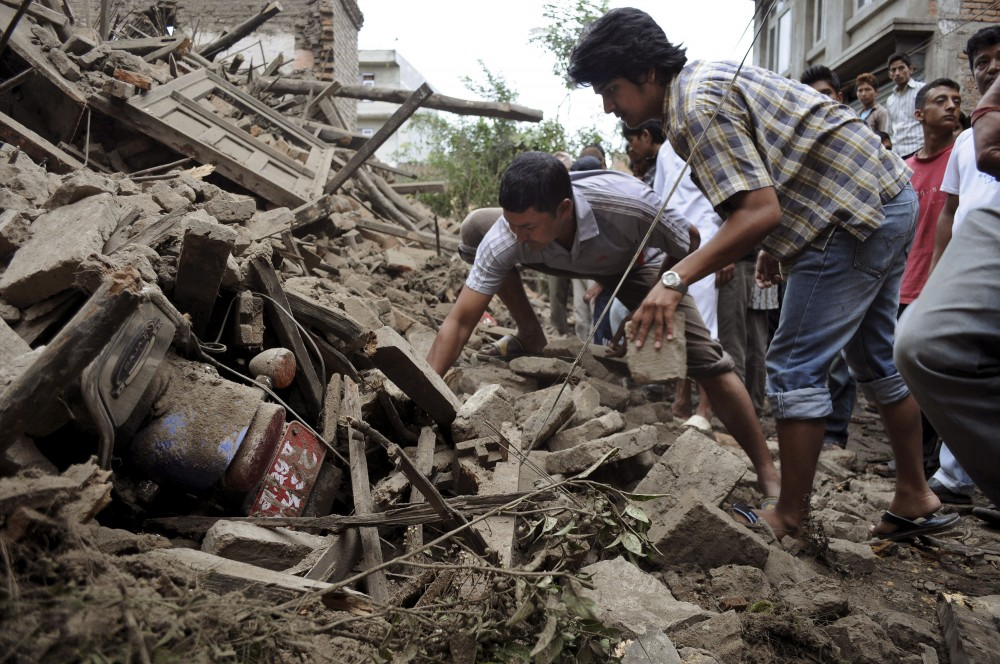 Nepalese people try to take out a motorbike buried under the debris o