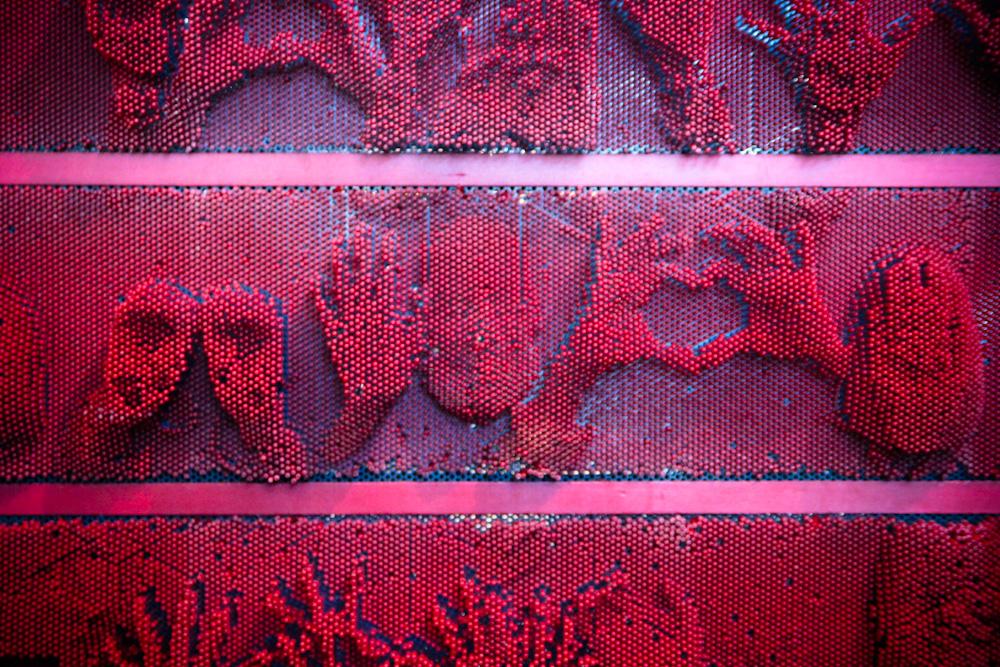 Niños y niñas juegan a dejar su huella en la pared de pixeles. © Plataforma Urbana.