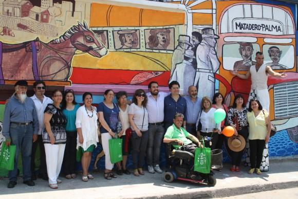 """Vecinos que participaron del programa """"Quiero mi Barrio"""" posan en frente al mural """"Medios de Transporte""""."""