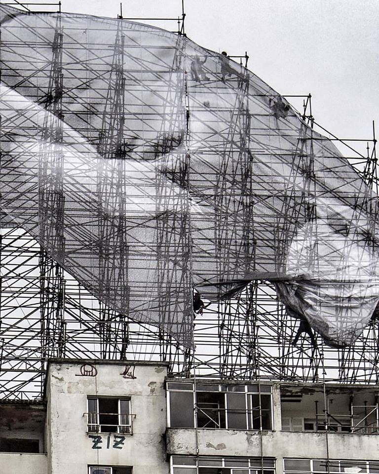 Imagen de Mohamed Younes Idriss saltando sobre edifício. Imagen © JR, vía Facebook del artista